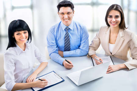 businessteam: A business team of four plan work in office Stock Photo