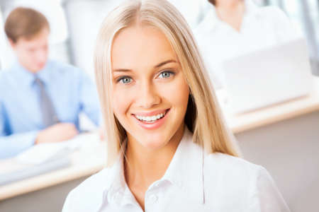 Pretty Caucasian business woman at office with colleagues on the background photo