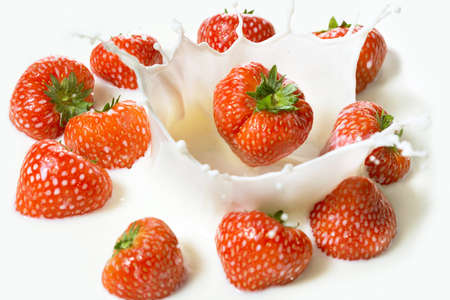 Red strawberry fruits falling into the milky splash photo