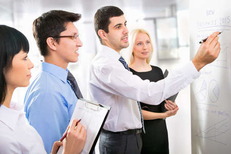 Boardroom meeting: Group of business people looking at the graph on flipchart Stock Photo