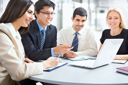boardroom meeting: A business team of four plan work in office Stock Photo