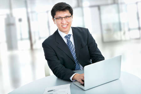 Happy business man sitting in front of laptop Stock Photo - 21253374