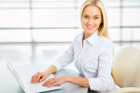 Portrait of a young business woman using laptop at office Stock Photo - 21258465