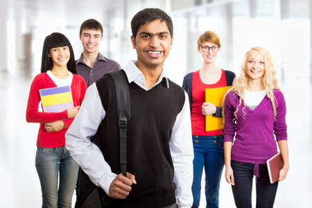 Young indian student and his diversity friends on background Foto de archivo