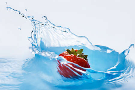 deeply: Strawberry falls deeply under water with a splash