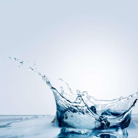 Mooie scheut water vallen van een schijfje citroen