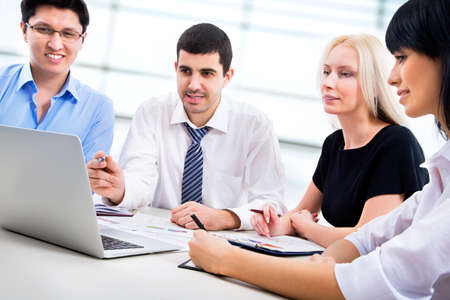 people working together: A business team of four plan work in office Stock Photo