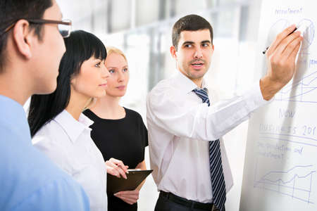Group of business people looking at the graph on flipchart Foto de archivo