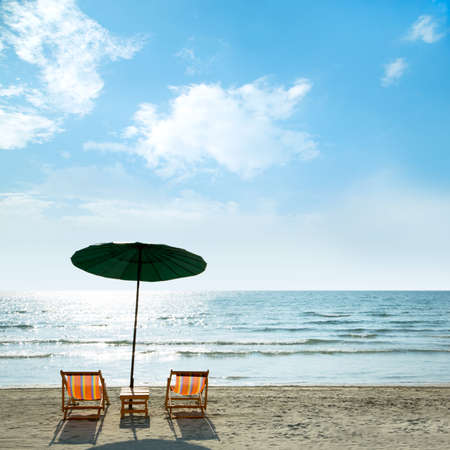 Beach chairs and umbrella on tropical sand beach. photo
