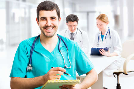 clinical staff: Portrait of a smart male doctor sitting in front of his team and smiling