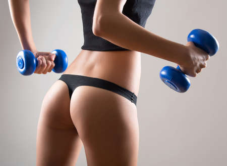 back exercise: Fitness woman. Slim woman with dumbbells. Stock Photo