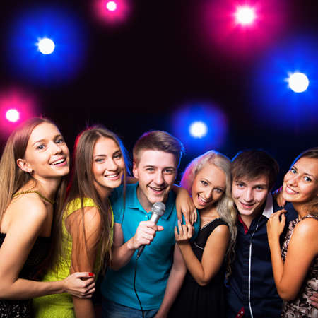 Young people singing into microphone at party photo