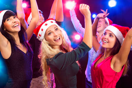 Happy people in Santa hats dancing at party photo