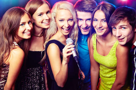Young people singing into microphone at party Stock Photo - 23220846