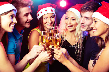 adult christmas: Happy group of young friends touching the glasses with each other Stock Photo
