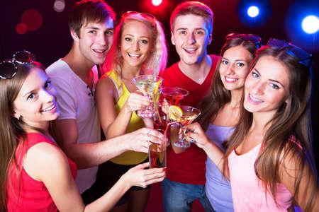 brindisi spumante: Le persone felici tintinnano da bicchieri con l'altro