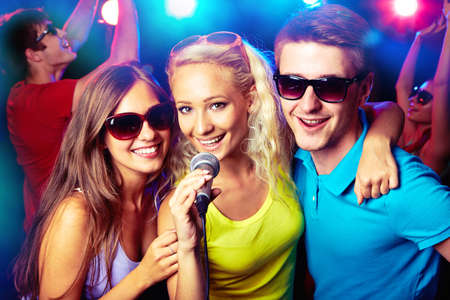people singing: Young people singing into microphone at party