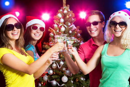 Happy people clinking by glases around the Christmas tree photo
