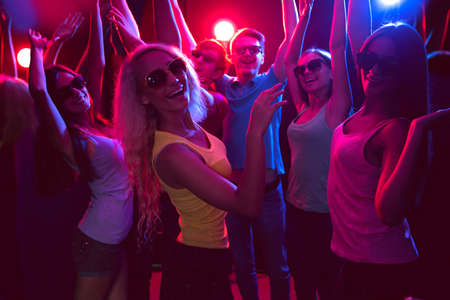 Young people having fun dancing in a nightclub photo