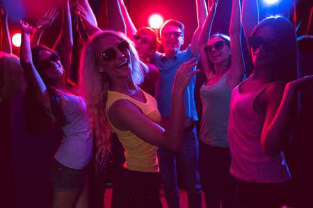 Young people having fun dancing in a nightclub photo