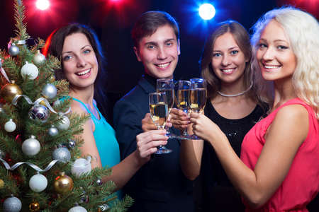 glases: Happy people clinking by glases around the Christmas tree