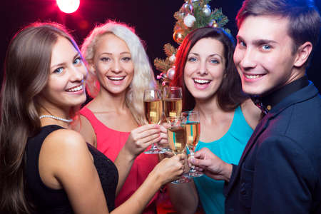 christmas drink: Happy people clinking by glases around the Christmas tree