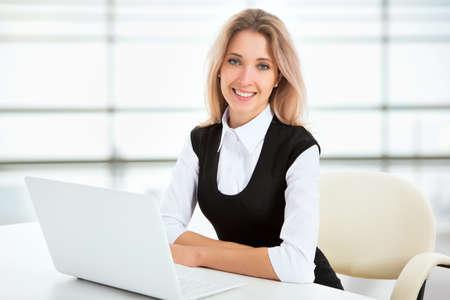 jornada de trabajo: Retrato de una joven mujer de negocios usando la computadora port�til en la oficina Foto de archivo