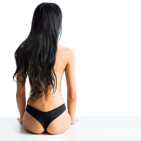 Slim topless woman sitting back and combs her beautiful hair photo