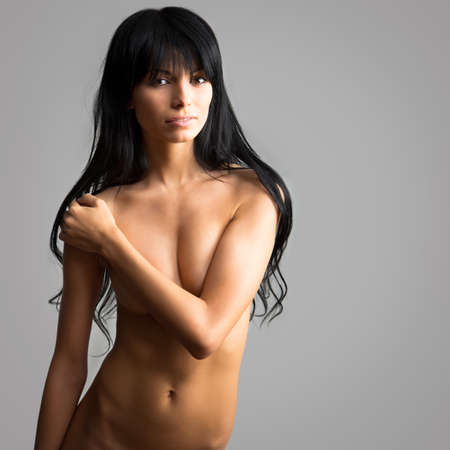 brunette naked: Beautiful woman covers her naked breasts with her hand
