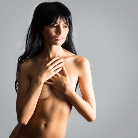naked lady: Beautiful woman covers her naked breasts with her hands Stock Photo