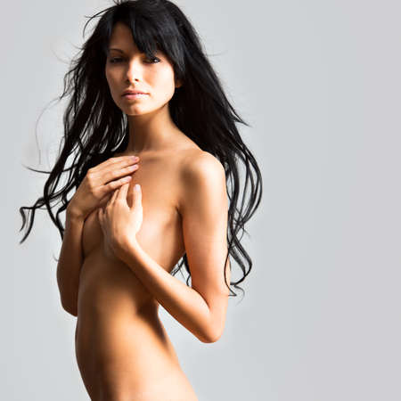 brunette naked: Beautiful woman covers her naked breasts with her hands Stock Photo