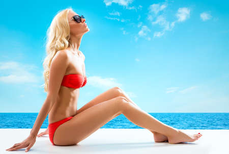 Sexy blonde woman sunbathing by the sea photo