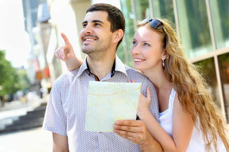 Young couple walking around the city holding a map photo