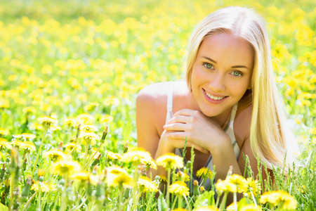 Beautiful young woman in a clearing among the flowers Stock Photo - 24849345