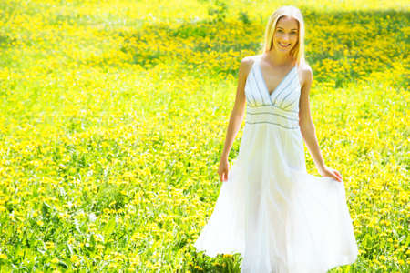 Beautiful young woman in a clearing among the flowers photo