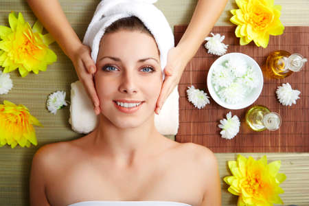 スパのサロンで女性の顔のマッサージをしているマッサージ師。美容治療の概念。