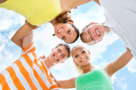 Group of happy young people in circle at beach have fun and smile photo