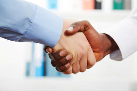 Businessmen shaking hands while in their office