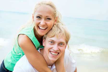 18's: Happy young couple embracing on summer beach, having fun together, laughing.