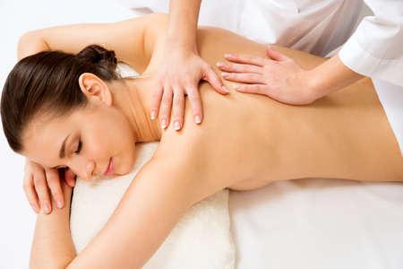 mimos: Masajista haciendo masaje en la espalda de la mujer en el salón de spa. Concepto de tratamiento de belleza.