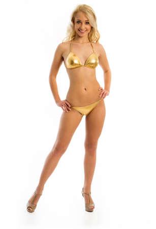 maillot de bain fille: Jeune fille blonde en bikini d'or sur fond blanc Banque d'images