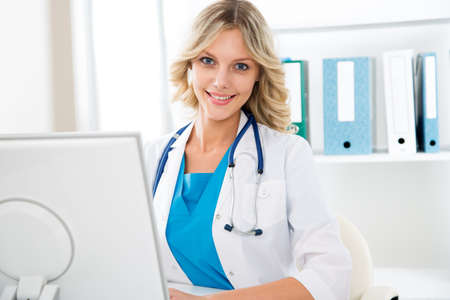 mature women only: Female doctor sitting at the desk with computer