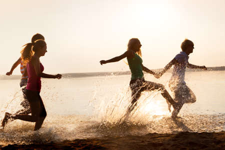 happy teenagers: Group of happy teenagers running through the water at the beach