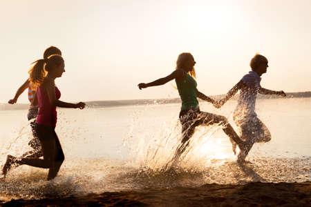 bewegung menschen: Gruppe gl�ckliche Teenager ausgef�hrt durch das Wasser am Strand