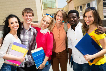 Group of diverse students outside smiling together Stock Photo