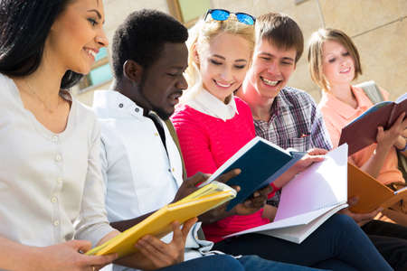 Group of university students studying reviewing homework photo