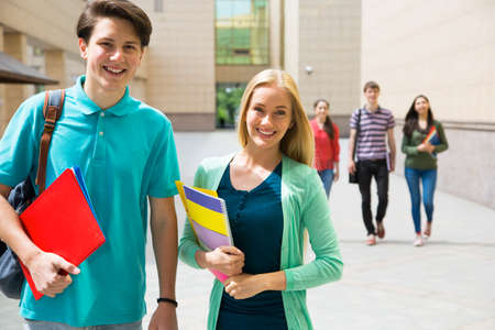 book bag: Happy college students walking together