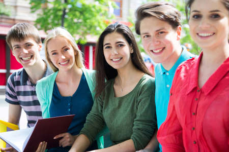 university text: Group of university students studying, reviewing homework in park Stock Photo