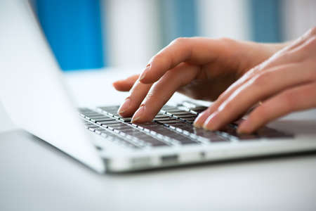 Closeup of businesswoman typing on laptop computer Imagens