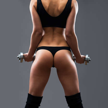 hands on hips: Back of fitness woman. Slim woman with dumbbells.